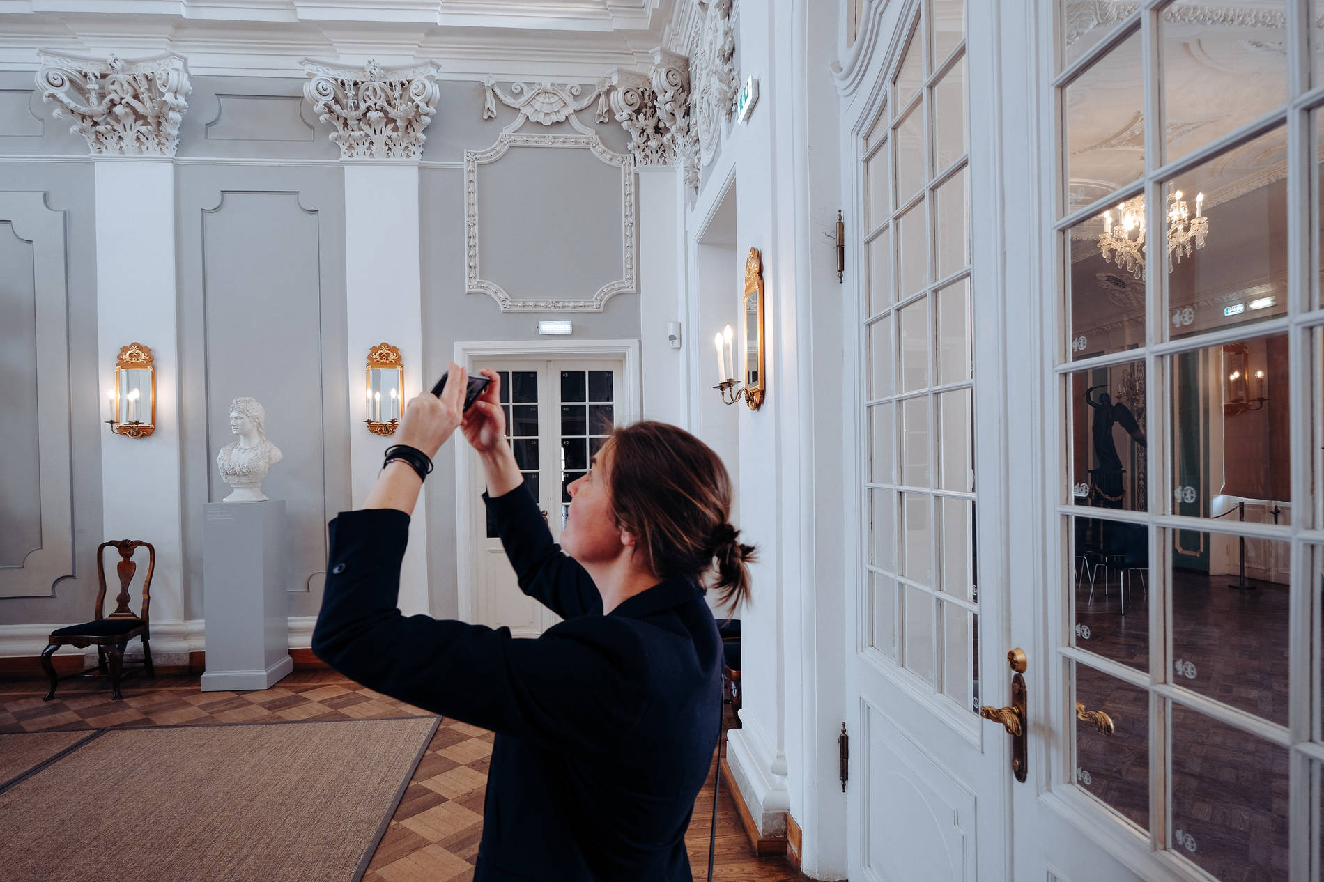 Woman taking a photo at the main hall of the Kadiorg Palace in Tallinn, Estonia